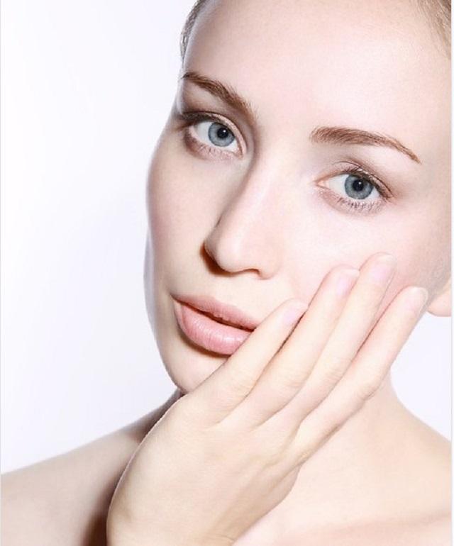czysta skóra kobiety, która trzyma się dłonią za twarz