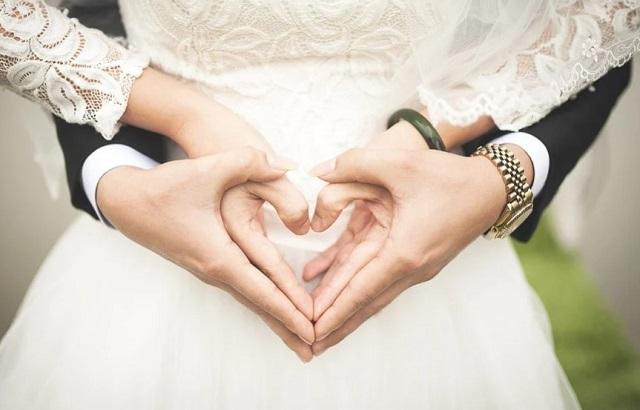 złączone dłonie pary na tle białej sukni