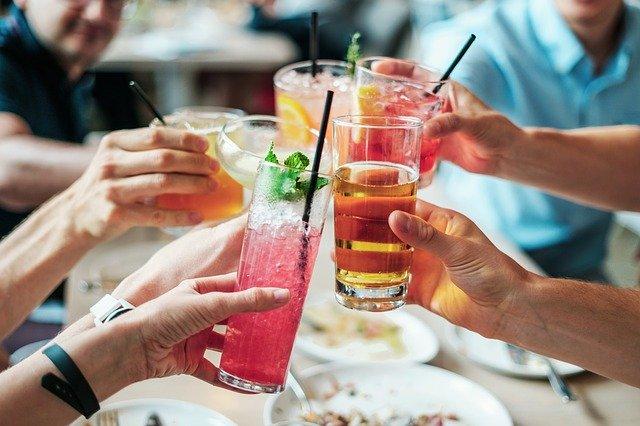 kolorowe drinki w dłoniach nad stołem