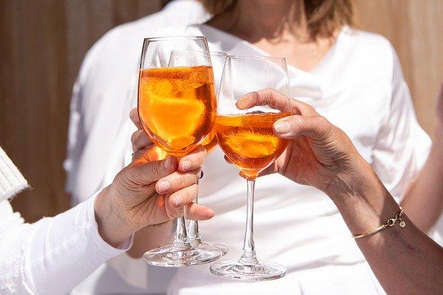 grupa ludzi w białych ubraniach trzyma drinki o pomarańczowym kolorze