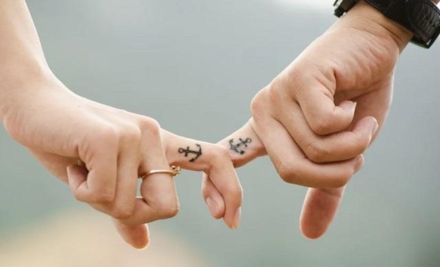 dwie dłonie i palce trzymające się siebie i tatuaże na wskazujących palcach