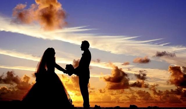 zachód słońca a na horyzoncie młoda para trzyma się za ręce