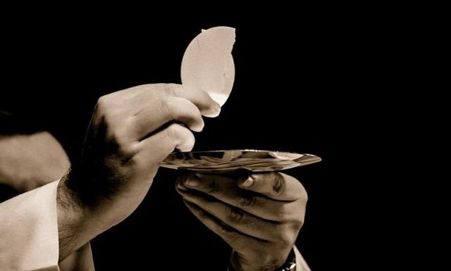 Komunia Święta na ciemnym tle z ręką księża