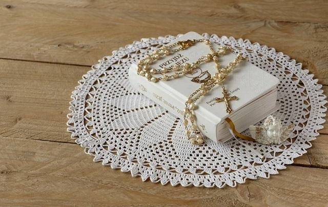 różaniec położy na książeczce, na stole z białym obrusem