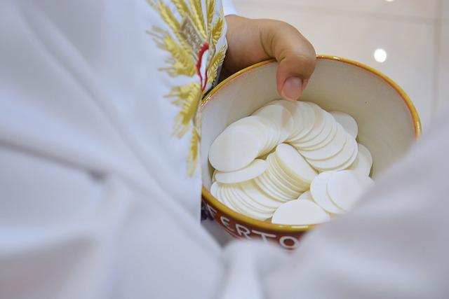 Ciało Boże w naczyniu trzymanym przez dłonie księdza