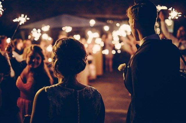 para młoda w towarzystwie gości weselnych o zmroku