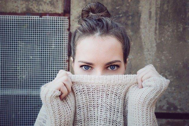 dziewczyna w spiętych włosach zasłania część swojej twarzy beżowym swetrem