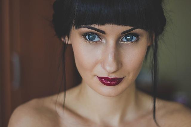 brunetka z grzywką i niebieskimi oczami bez bluzki patrzy w dal ma burgundowe usta