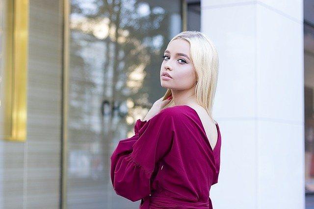 elegancka blondynka stoi tyłem w fuksjowej sukience