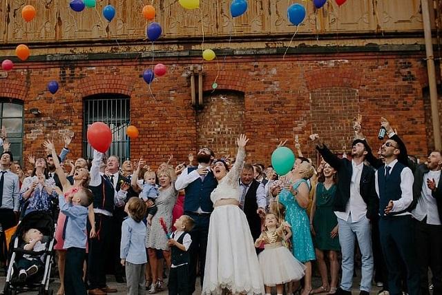 zadowoleni goście i para młoda podrzucają balony