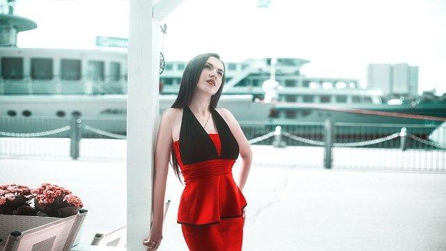 brunetka stoi na ulicy w czerwono-czarnej sukience