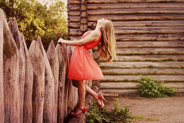 kobieta w czerwonej sukni łapie się za płot i odchyla do tyłu