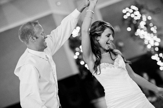 czarno białe zdjęcie panny młodej która uśmiecha się i tańczy z panem młodym bez marynarki