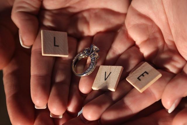 napis LOVE ułożony na dłoniach z drewnianych puzzli
