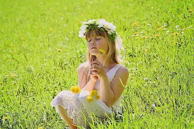 dziewczynka z wiankiem na głowie i w białej sukience siedzi na łące