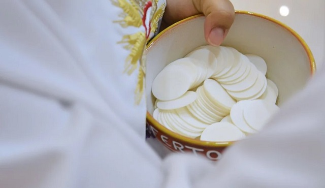 eucharystia w naczyniu z dłonią księdza