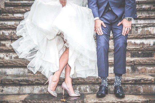 szpilki na nogach panny młodej i uniesiona sukienka oraz pan młody w kolorowych skarpetach na schodach