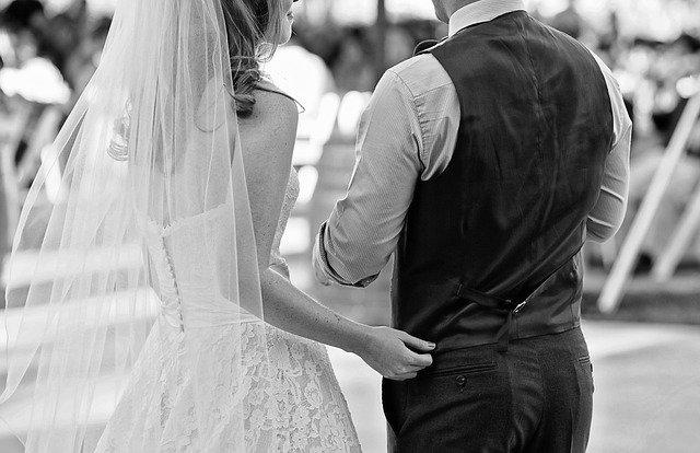 czarno białe zdjęcie pary młodej od tyłu gdy się obejmuje
