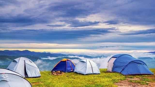 namioty niebieskie obok siebie pod błękitnym niebem