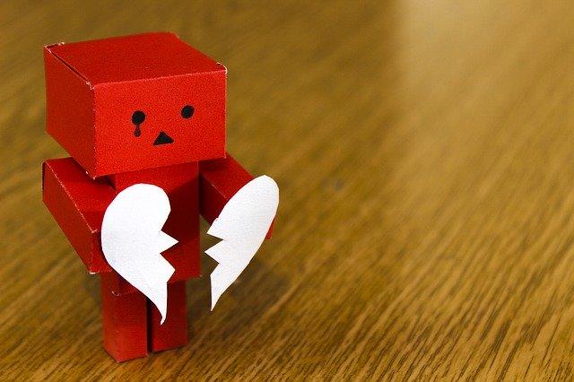 czerwony ludzik trzymający rozdarte białe serce