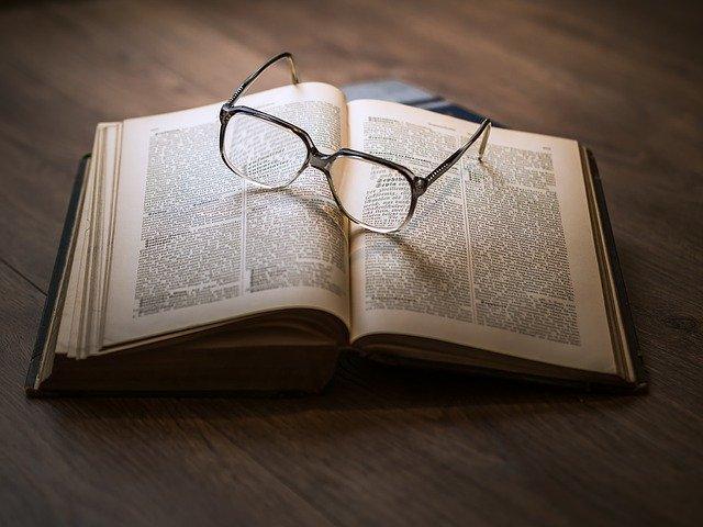 okulary położone na rozłożonej książce