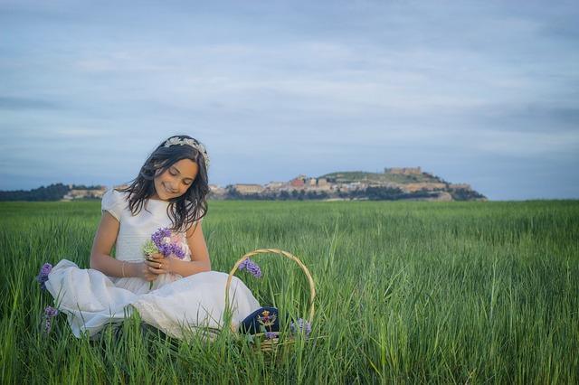 dziewczynka  w komunijnej sukience i wianku siedzi na łące