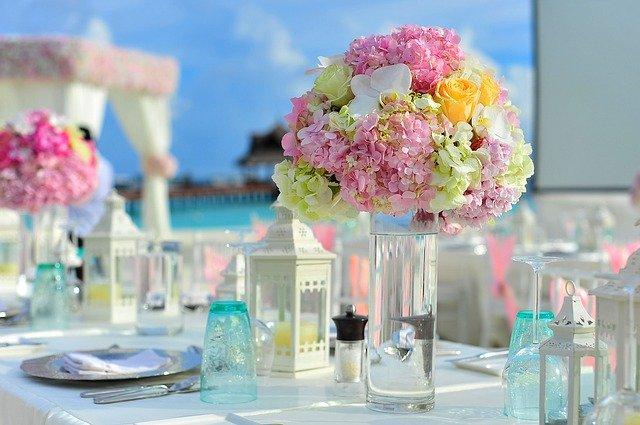 pastelowe zdjęcie z jasną zastawą na stole i kolorowymi kwiatami