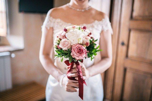panna młoda w białej sukni i z bukietem ślubnym