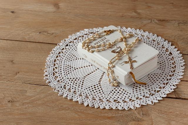 modlitewnik komunijny na białej serwecie na stole