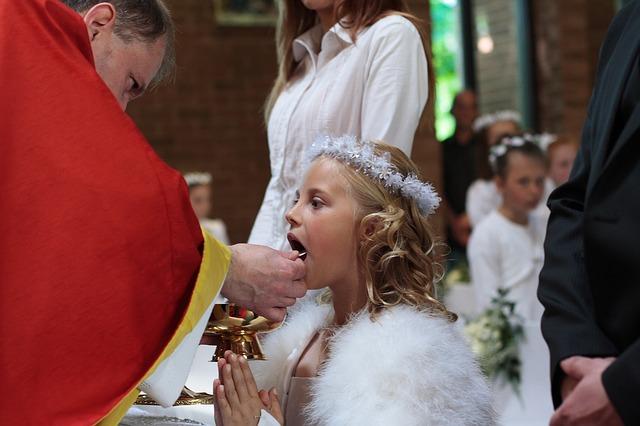 dziewczynka w czasie Pierwszej Komunii Świętej w białej sukni i w wianku