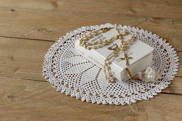 biały modlitewnik na białej serwetce, która leży na stole