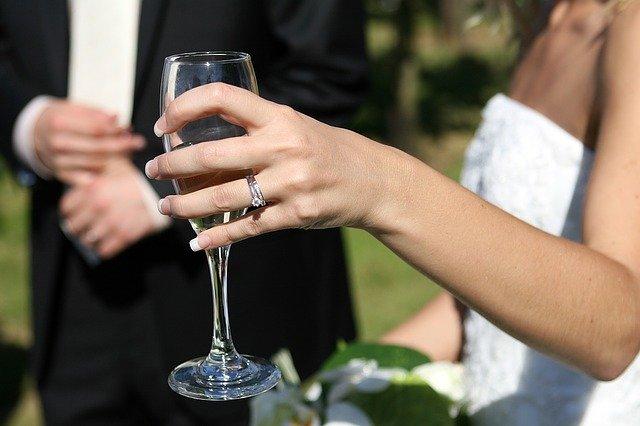 panna młoda w dłoni trzyma lampkę szampana
