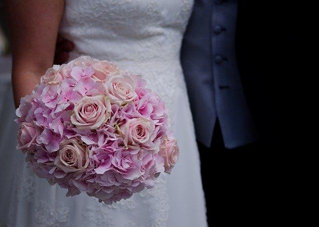 różowy bukiet ślubny na tle białej sukienki