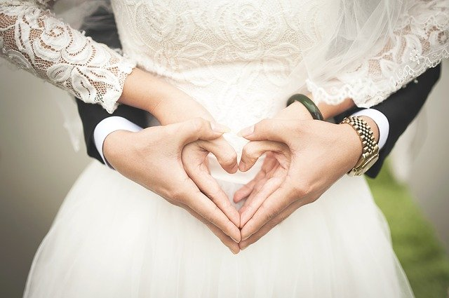 ułożone serce z dłoni na tle białej sukni ślubnej