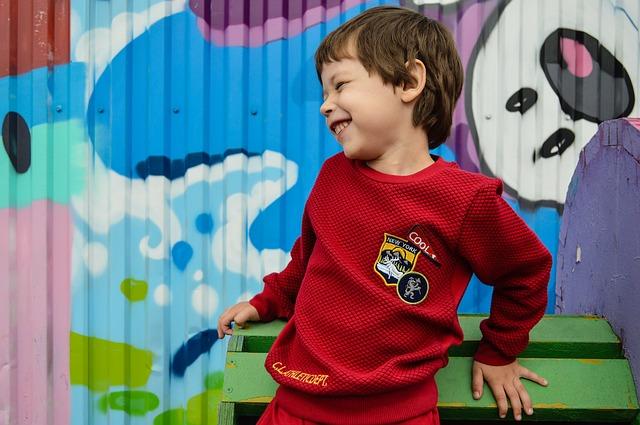 uśmiechnięty chłopiec w czerwonej bluzie stoi na tle graffiti