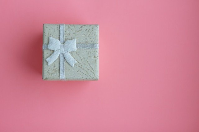 biały prezent zapakowany wstążką na różowym tle