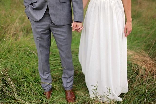 nogi pana młodego w szarym garniturze i panna młoda cała w bieli