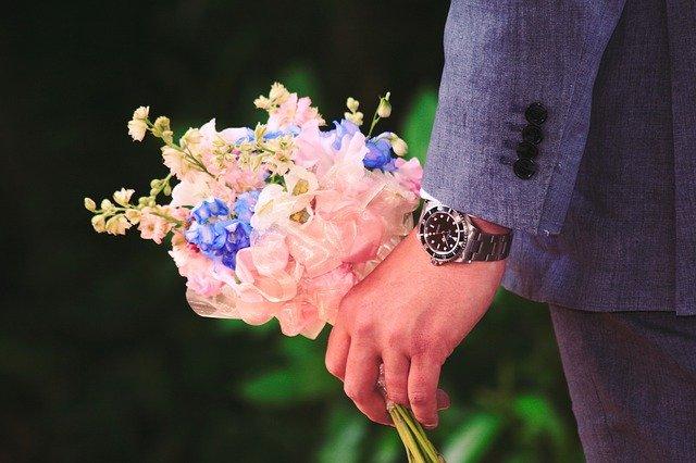 mężczyzna trzyma kwiaty w dłoni