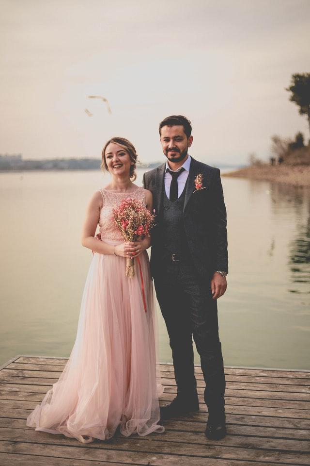 pan młody i panna młoda w różowej sukni na tle wody