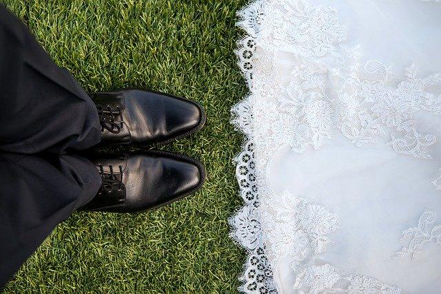 buty czarne męskie obok dołu białej sukni ślubnej ułożone na zielonej trawie