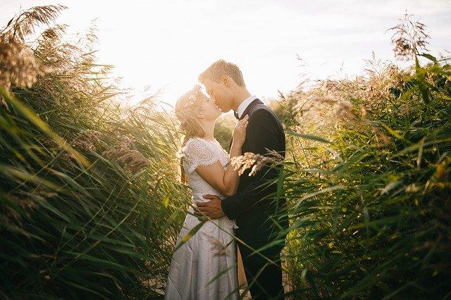 całująca się młoda para w wysokiej trawie
