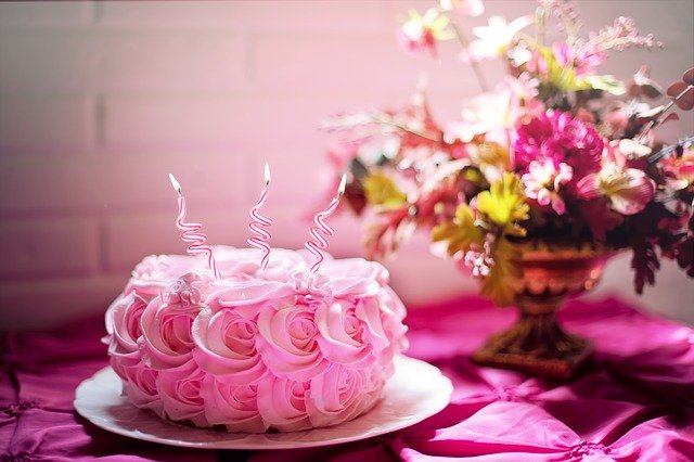 różowy tort z trzema świeczkami