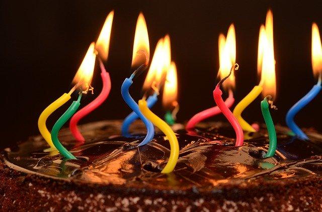 wygięte kolorowe świeczki w czekoladowym torcie