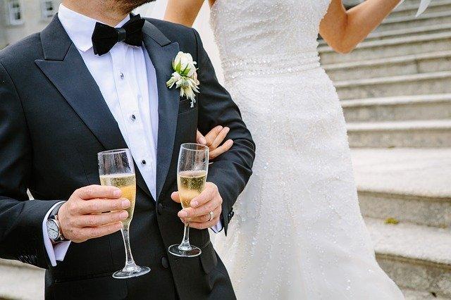 pan młody w czarnym garniturze trzyma szampana a obok niego stoi panna młoda w białej sukni