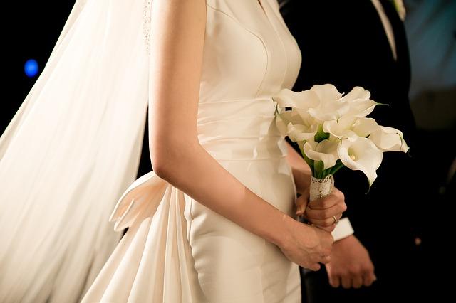 panna młoda w kremowej sukni ślubnej z beżowym bukietem w dłoni obok pana młodego