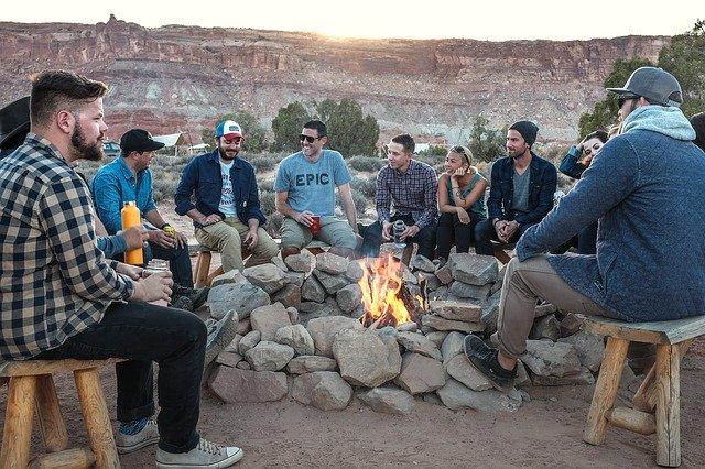grupa uśmiechniętych ludzi przy ognisku