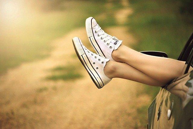 nogi w białych trampkach wystawione przez okno auta w słoneczny dzień