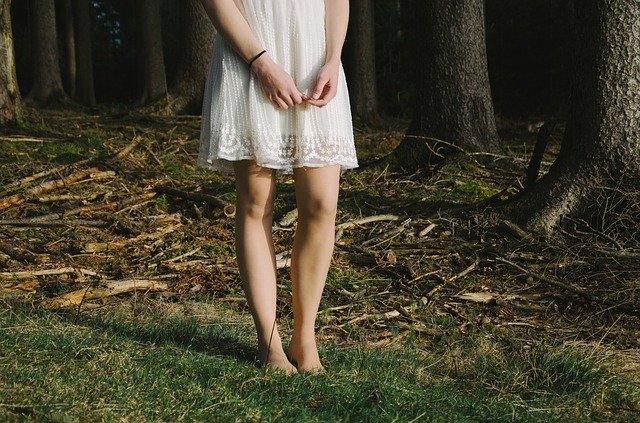 zagubiona dziewczyna w lesie na boso w białej sukience trzyma ręce splecione luźno przed sobą