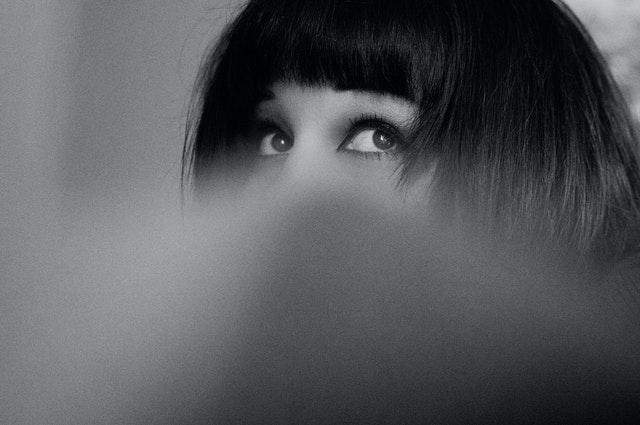 czarno-białe zdjęcie kobiety widoczne tylko oczy i grzywka