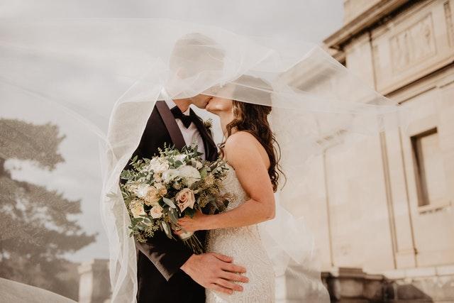 para młoda całuje się pod długim welonem panny młodej, która w dłoni trzyma bukiet z jasnych kwiatów